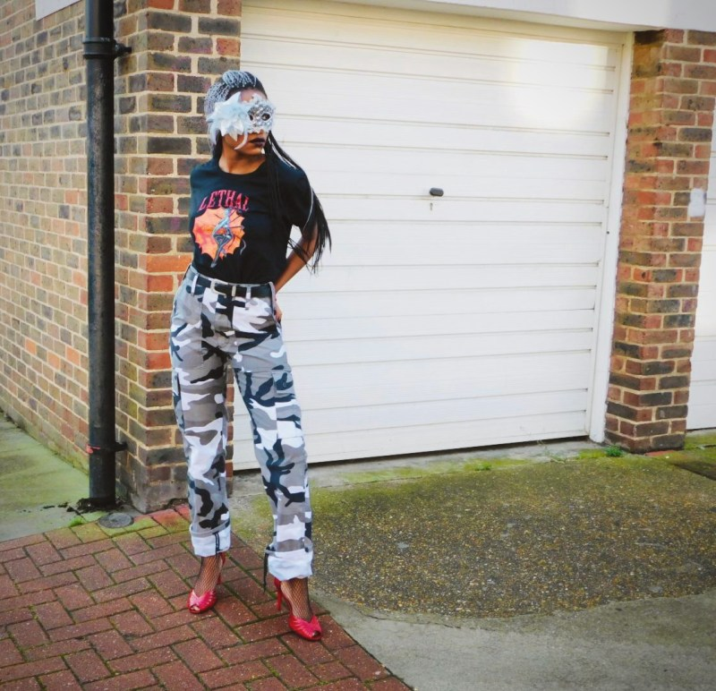 Model stands in front of white garage. She is wearing a black graphic tee with the slogan 'Lethal', grey camouflage cargo trousers and pillarbox red peep-toe stiletto heels. She also has a silver masquerade mask covering her eyes.