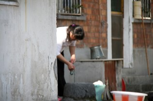 Dans une rue à l'écart, une femme fait son linge au puit