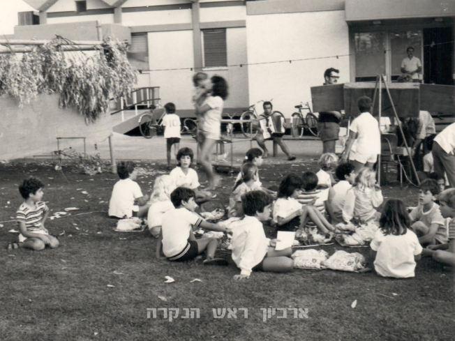 """סוכות 1974, צילמה: רות שחר ז""""ל. ילדי דקל וכלנית, שמחי עם האקורדיון, גיל לבני ליד ארון החשמל"""