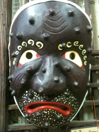 A gorgeous theatrical mask handcarved and displayed in the artisan's shop.