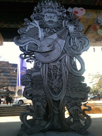 A huge guardian at a famous shrine's entry way, carved of wood.