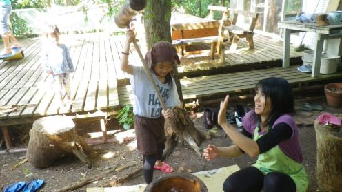 Umi, sporting a monkey costume, pounds mochi while her mother, Chika, jokingly cringes. That hammer is heavy! The mochi is a mound of glutinous rice, nestled in a sturdy carved-out tree trunk.