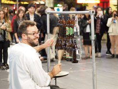a guy playing beer bottles with wooden spoons