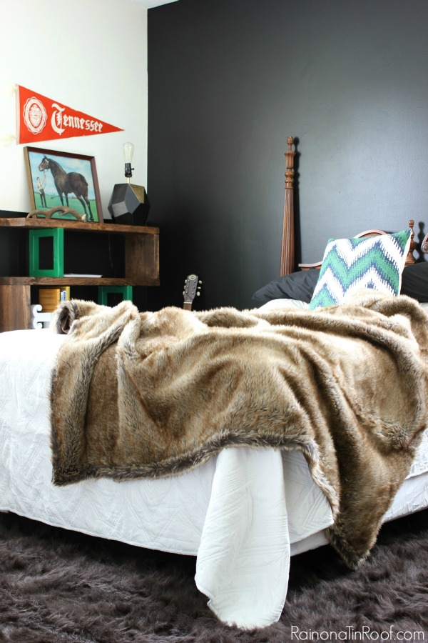 Masculine Bedroom Makeover - This room functions as a Guest Room, Teenage Boy's Room, and an Office. Lots of great ideas for making a room function for multiple uses. Black Walls (Behr's Limousine Leather), Faux Fur Throw / Green Accents
