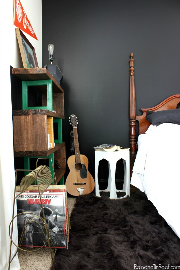 Masculine Bedroom Makeover - This room functions as a Guest Room, Teenage Boy's Room, and an Office. Lots of great ideas for making a room function for multiple uses. DIY Bookshelf / Guitar as decor / White Geometric Side Table / Black Walls (Behr's Limousine Leather)
