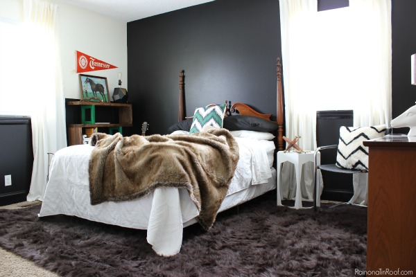 Masculine Bedroom Makeover - This room functions as a Guest Room, Teenage Boy's Room, and an Office. Lots of great ideas for making a room function for multiple uses. Black Walls (Behr's Limousine Leather), Black and White with green and wood toned accents. Brown Faux Fur Rug
