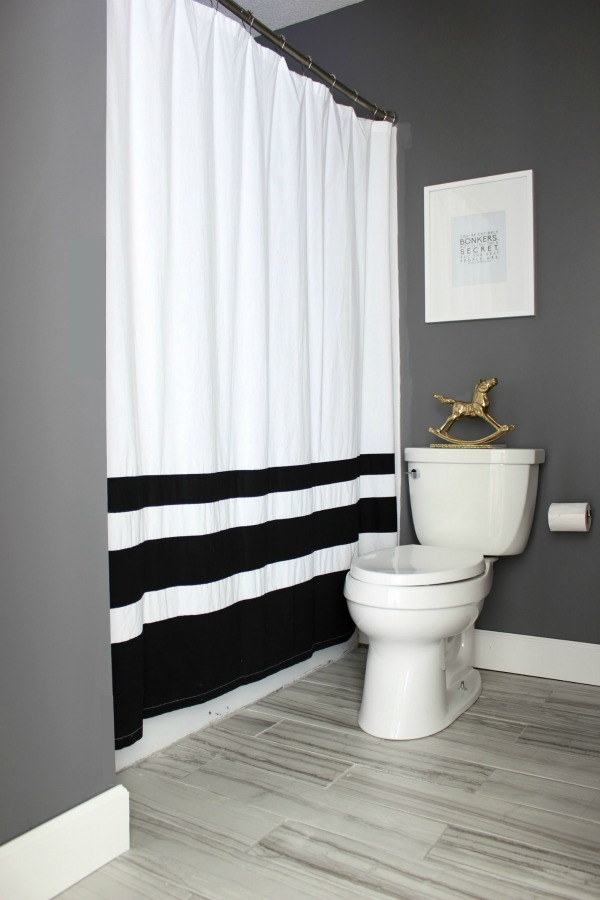 Such an adorable bathroom for a kid, but also stylish for adults! The 70's Landing Pad Hall Bathroom Remodel | Gray Walls / Black and White Decor / Kid's Bathroom / Gray Rectangle Floor Tiles