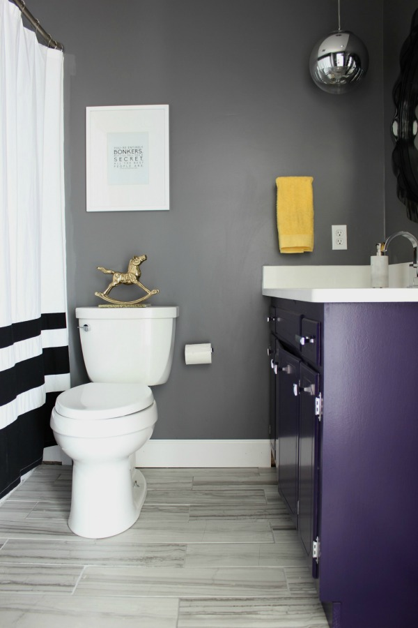 Such an adorable bathroom for a kid, but also stylish for adults! The 70's Landing Pad Hall Bathroom Remodel | Gray Walls / Black and White Decor / Kid's Bathroom / Purple Bathroom Vanity / Gray Rectangle Floor Tiles