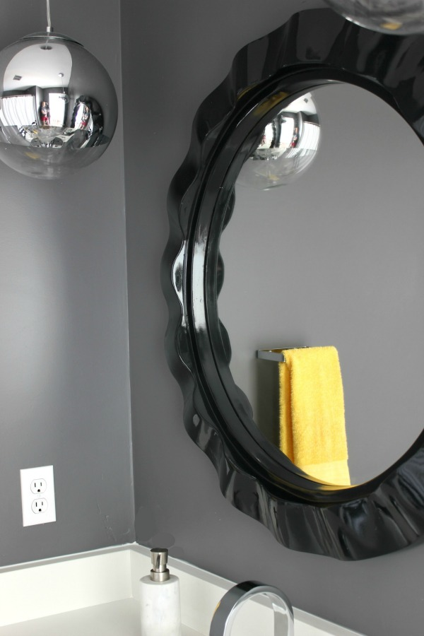 Such an adorable bathroom for a kid, but also stylish for adults! The 70's Landing Pad Hall Bathroom Remodel | Gray Walls / Black and White Decor / Kid's Bathroom / Curvy Black Round Mirror / Retro Pendant Lights