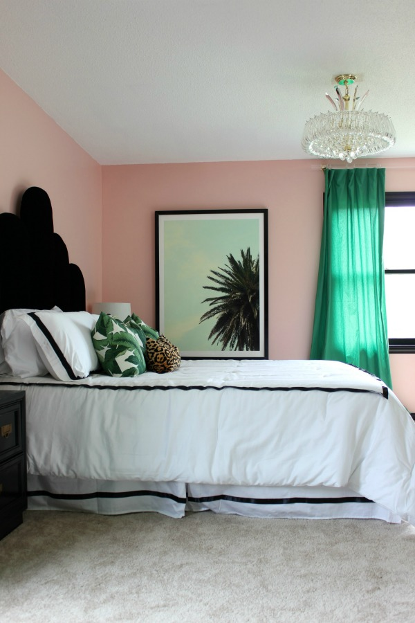 This master bedroom makeover is a MUST-SEE! Who knew pink could look so good?! It's an eclectic vibe of old Hollywood glamour meets Palm Beach decorating styles! The 70's Landing Pad Home Tour, Part 2: The Master Bedroom | Palm Tree Art | DIY Scalloped Headboard