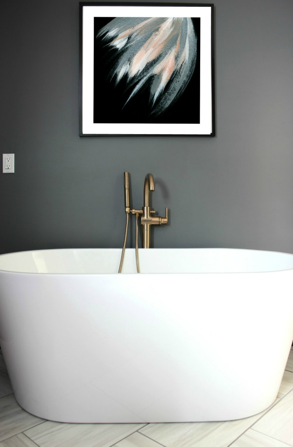This bathroom remodel is gorgeous. It's a great combination of masculine and feminine design perfectly balanced. Black, Gray, and Brass Master Bathroom Remodel | Dark Gray Walls | Art above Bathtub | Brass Fixtures | Brass Bathtub Faucet | Oval Freestanding Bathtub