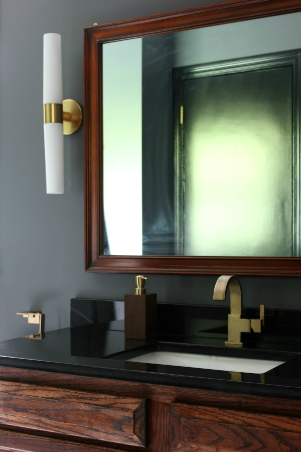 This bathroom remodel is gorgeous. It's a great combination of masculine and feminine design perfectly balanced. Black, Gray, and Brass Master Bathroom Remodel | Dark Gray Walls | Black Trim | Stained Vanity | Brass Faucet | Black Granite Counter | Brass Sconces