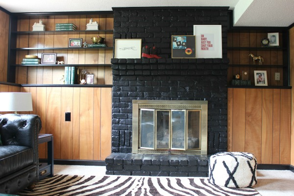 The Jungle Room Den Makeover inspired by Elvis' Jungle Room: They kept the paneling and it actually looks good with the black trim! | Painted Fireplace | Paneled Walls | Black Interior Design