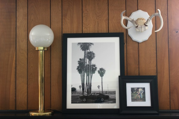 The Jungle Room Den Makeover inspired by Elvis' Jungle Room: They kept the paneling and it actually looks really good with the black trim! | Vintage Brass Lamp | Antlers | Palm Beach Art