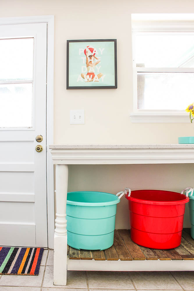Laundry Room Ideas - Island for folding clothes with buckets for storage underneath.