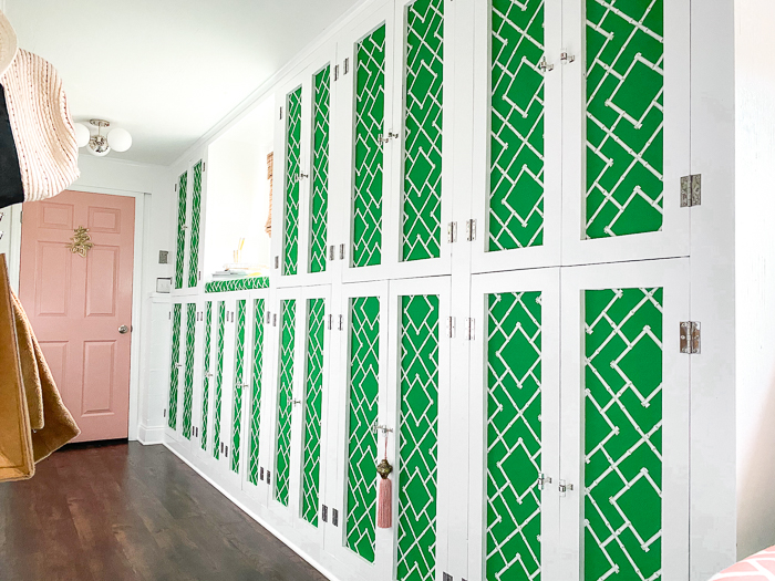 Green and White Mudroom cabinets with fabric inserts.