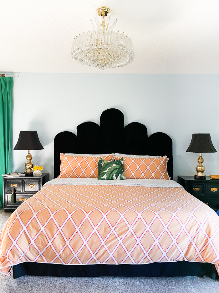 Bedroom with crystal chandelier, blue walls, black velvet headboard, orange bedding and green curtains.