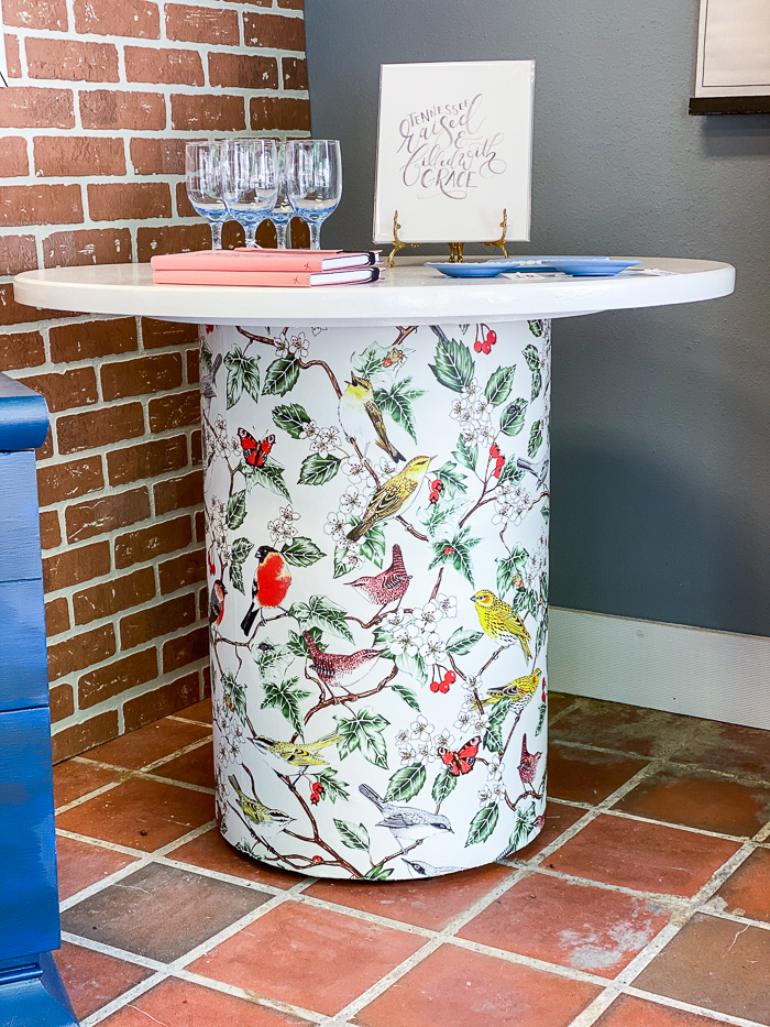 Wallpapered Furniture - white table with colorful bird wallpaper on table base.