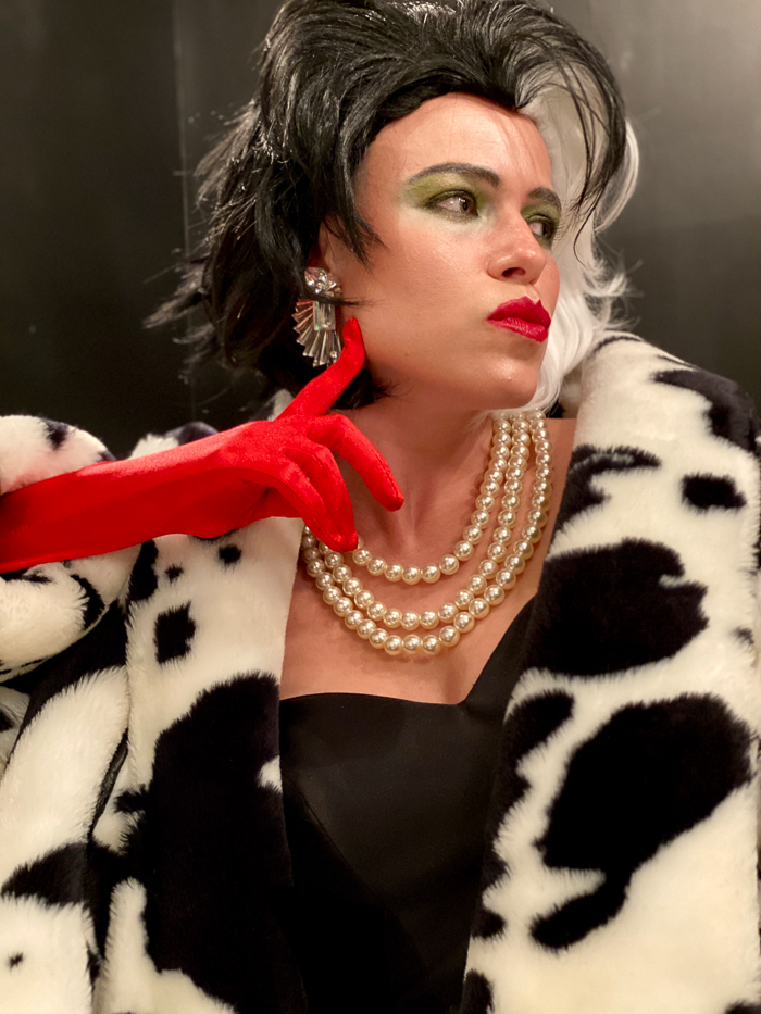Cruella Costume DIY with black and white wig, accessories and makeup.
