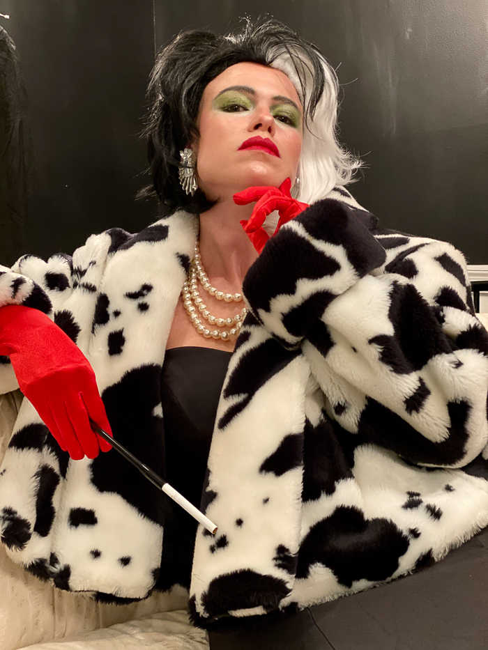 Cruella Costume with black and white fur coat, long black dress and red gloves.