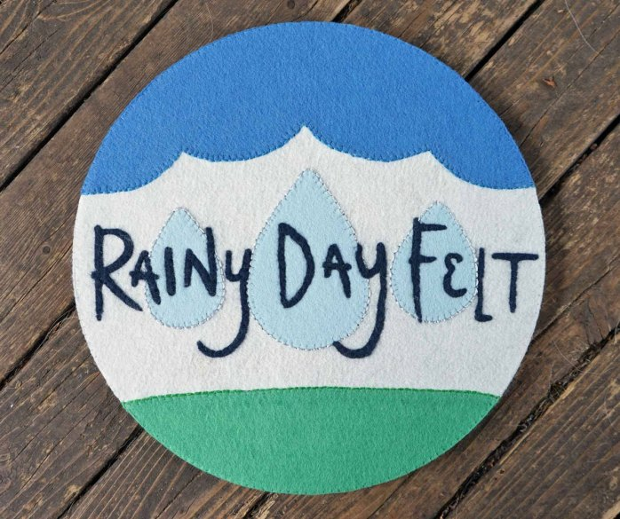 Rainy Day Felt logo wall decoration completed, laying on rustic wood