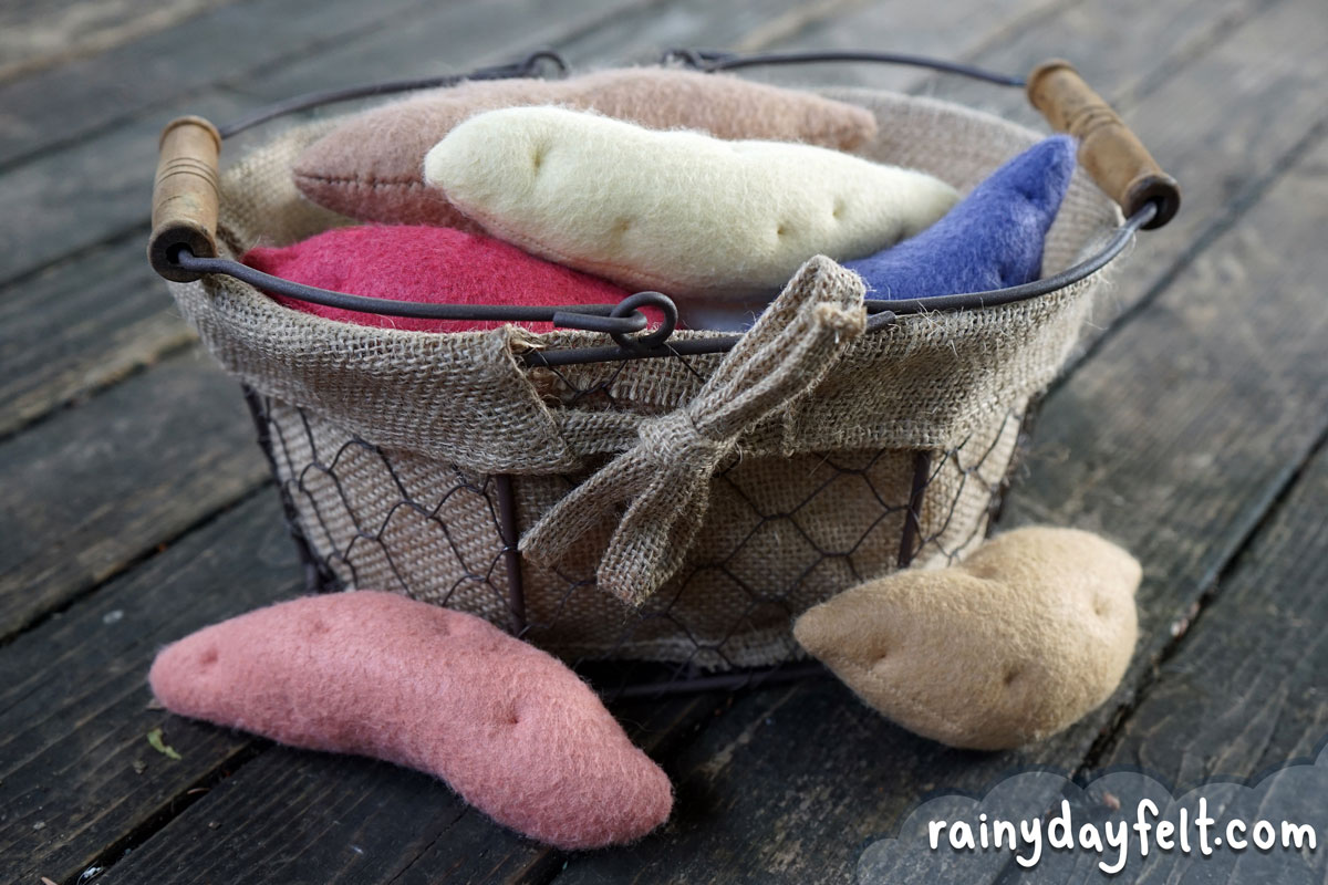 A basket of completed felt sweet potatoes, in bonita, garnet, jewel, purple, and white varieties