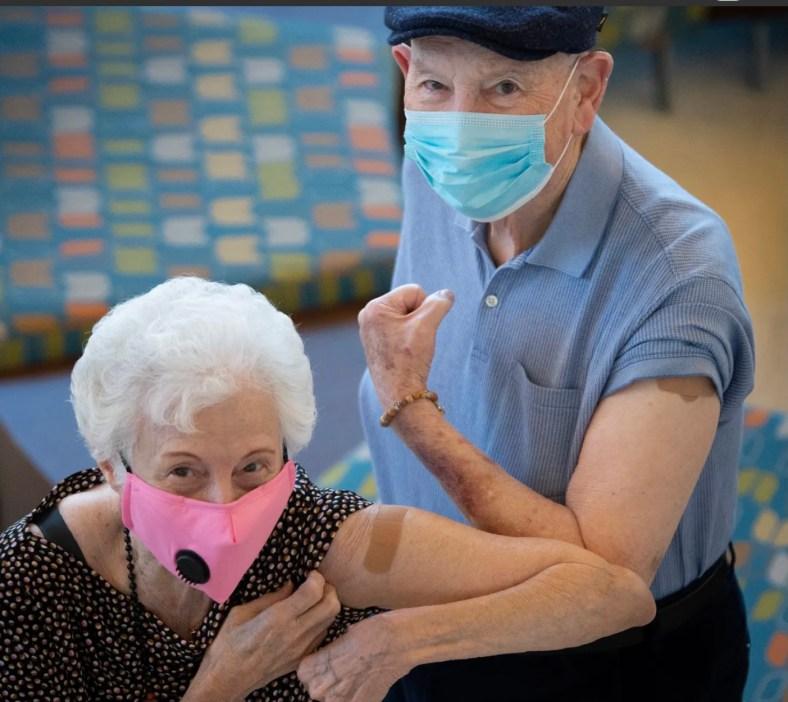 An elderly couple show off their coronavirus vaccine bandaids.
