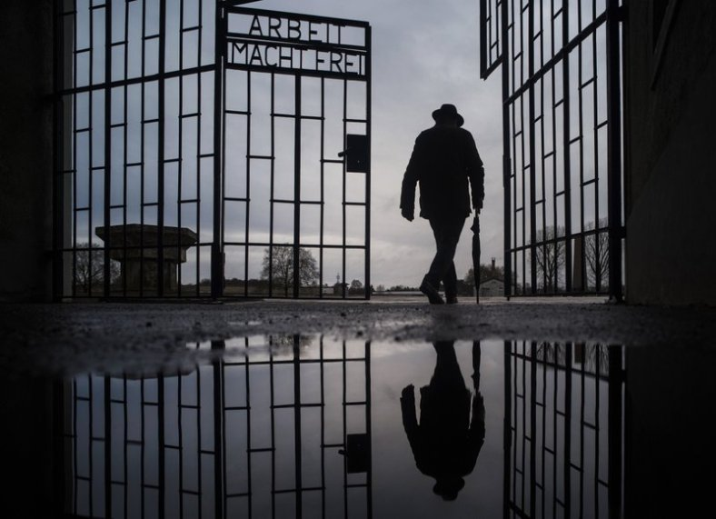File - In this Sunday, Jan. 27, 2019 file photo a man walks through the gate of the Sachsenhausen Nazi death camp with the phrase 'Arbeit macht frei' (work sets you free) during International Holocaust Remembrance Day. (AP Photo/Markus Schreiber, file)