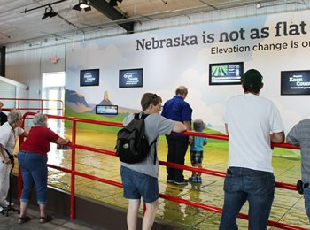 People standing a railing overlooking a giant map of Nebraska on the floor.