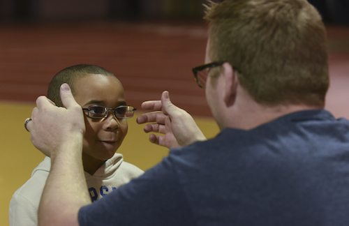 Man putting glasses on a child