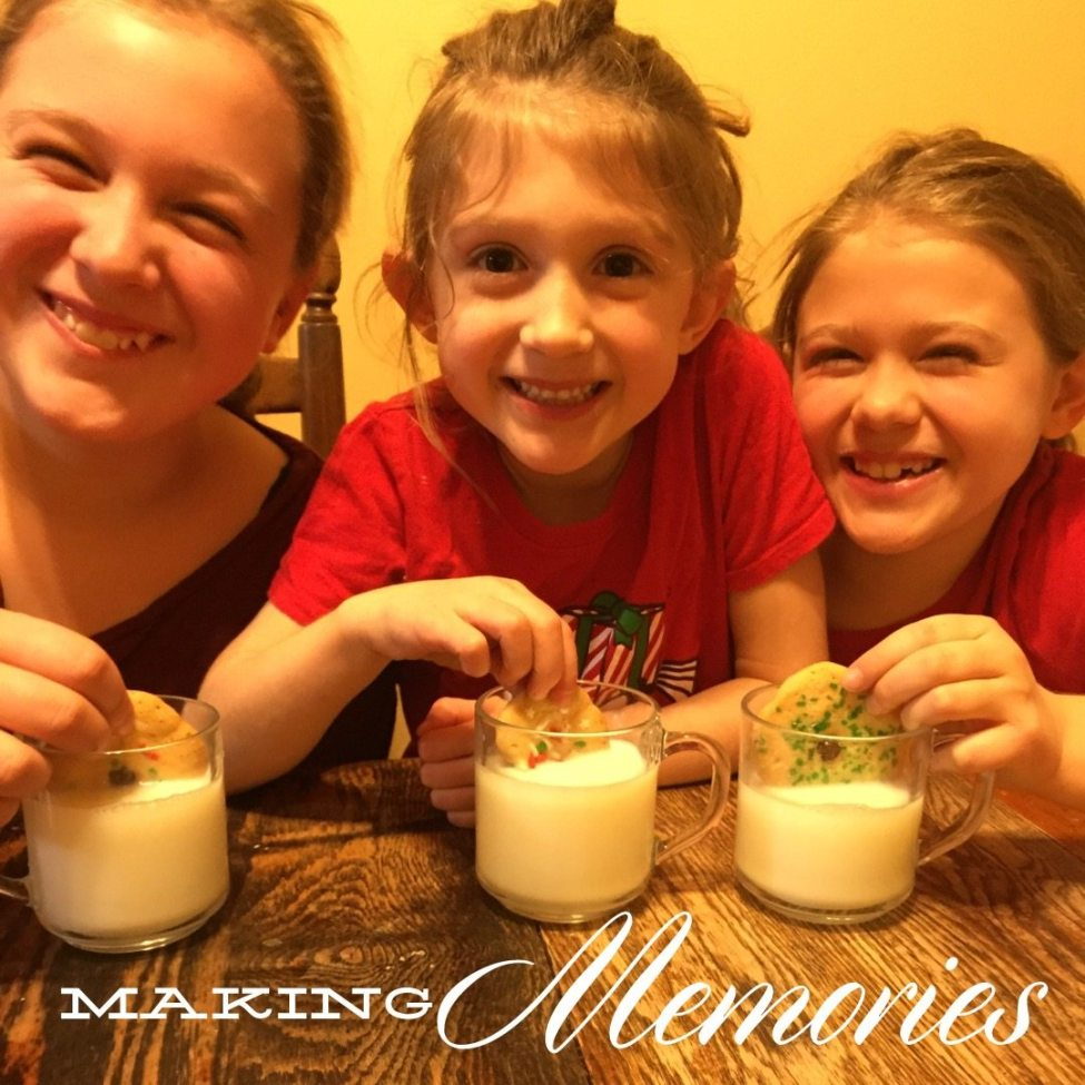 Mom and two daughters having milk and cookies.