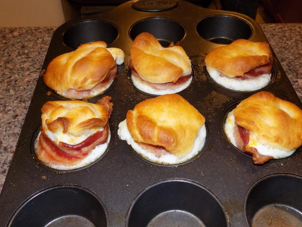 Cooked breakfast sandwiches in muffin tin.