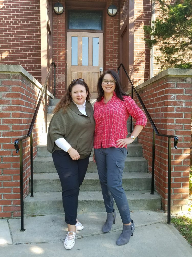 Two women standing in front of steps