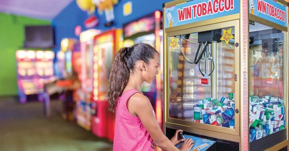 Girl playing a Win Tobacco claw game.