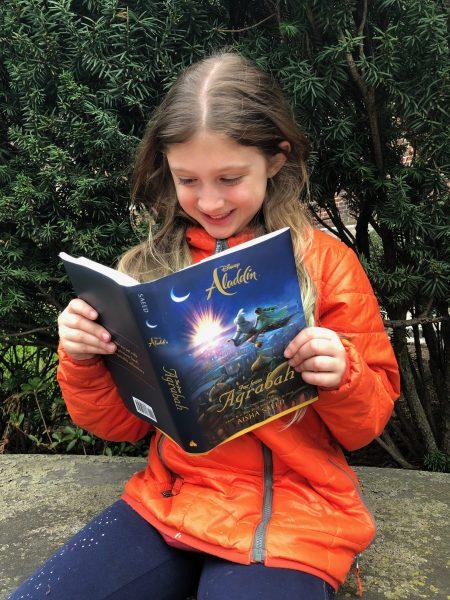 Girl reading Aladdin Far From Agrabah.