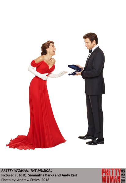Woman in red dress laughing with man in tuxedo.