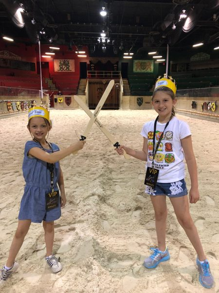 Girls crossing wooden swords at Medieval Times.