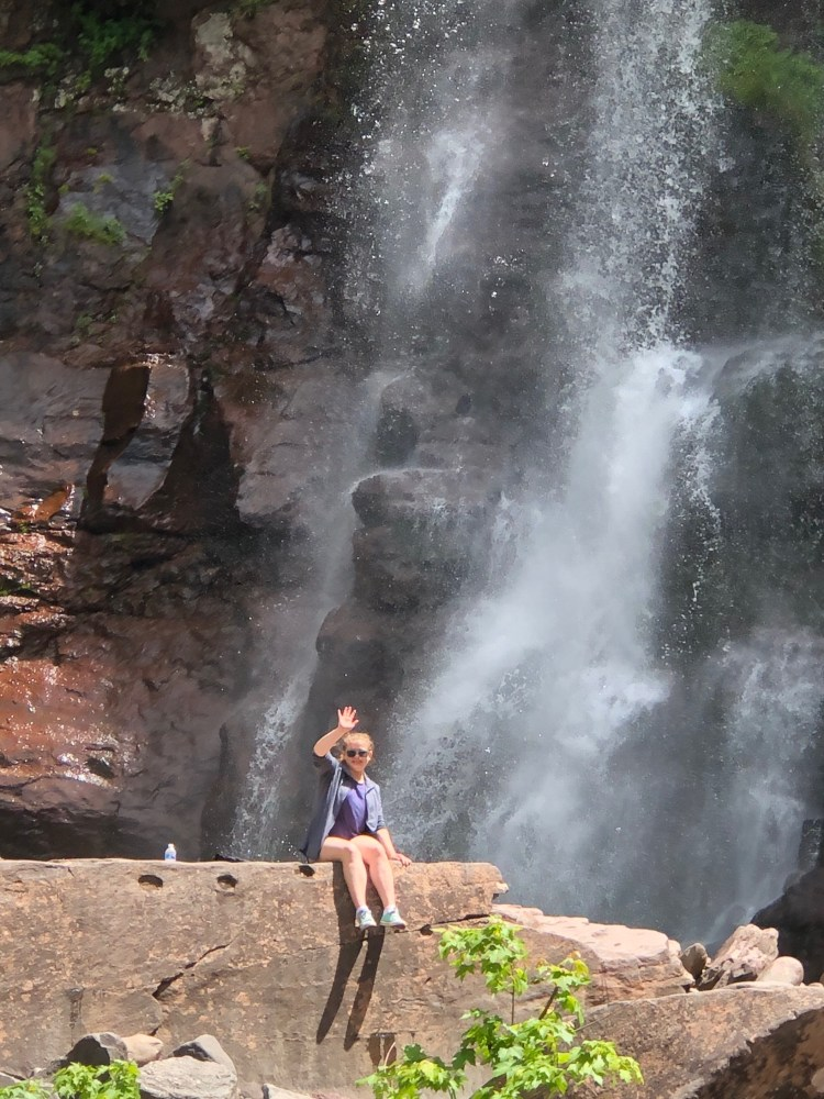 Girl sitting on huge rock in front of a waterfall.