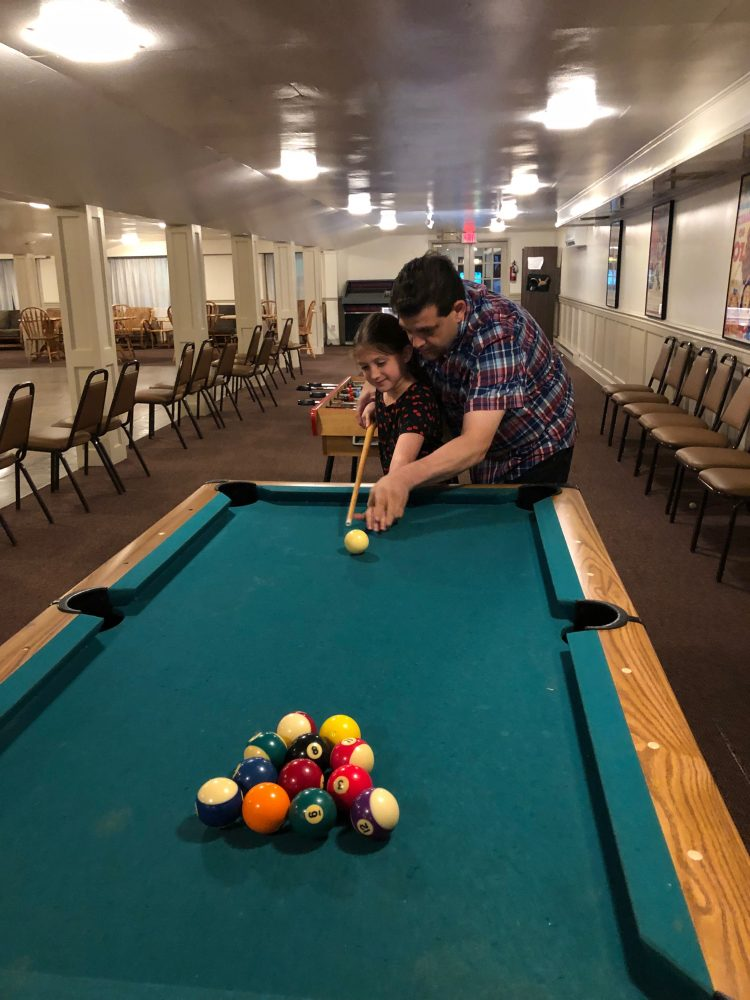 Father and daughter playing pool.
