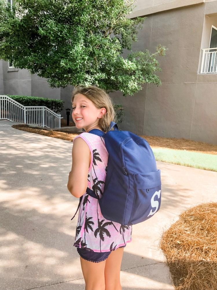 Girl wearing monogrammed backpack.