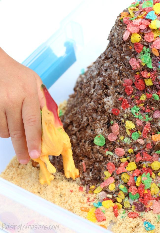 Dinosaur Sensory Bin with Edible Volcano   Fun kids activity and snack in one! DIY Dinosaur Sensory Bin + Edible Volcano Recipe with Cocoa & Fruity Pebbles - Sensory play idea for kids. This preschool sensory play idea is non toxic and edible for kids - #Recipe #SensoryPlay #Preschool #KidsActivities