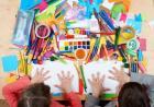 Zdjecie przedstawia dzieci malujące w zeszytach
