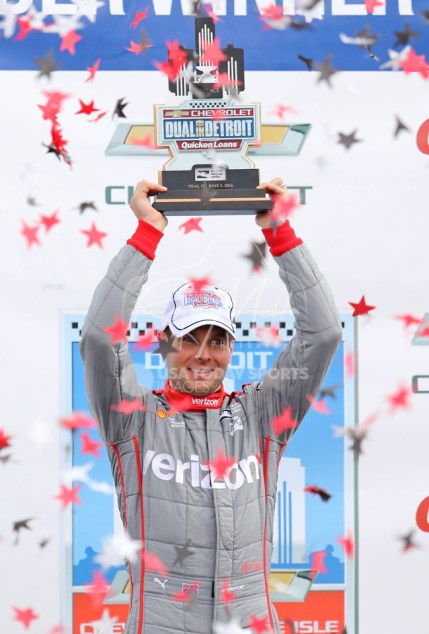 Jun 5, 2016; Detroit, MI, USA; Team Penske driver Will Power (12) of Great Britain lifts the first place trophy after winning the Chevrolet Dual in Detroit Race 2 at The Raceway at Belle Isle Park. Mandatory Credit: Raj Mehta-USA TODAY Sports