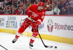 Feb 24, 2018; Detroit, MI, USA; Detroit Red Wings defenseman Xavier Ouellet (61) hits the puck around the boards during the first period against the Carolina Hurricanes at Little Caesars Arena. Mandatory Credit: Raj Mehta-USA TODAY Sports