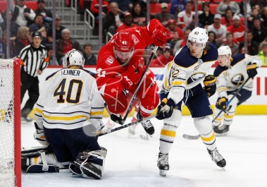 Feb 22, 2018; Detroit, MI, USA; Detroit Red Wings right wing Luke Glendening (41) gets tripped by Buffalo Sabres defenseman Nathan Beaulieu (82) in front of goaltender Robin Lehner (40) and during the second period at Little Caesars Arena. Mandatory Credit: Raj Mehta-USA TODAY Sports