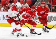 Feb 24, 2018; Detroit, MI, USA; Detroit Red Wings left wing Tomas Tatar (21) and Carolina Hurricanes right wing Justin Williams (14) fight for the puck during the third period at Little Caesars Arena. Mandatory Credit: Raj Mehta-USA TODAY Sports