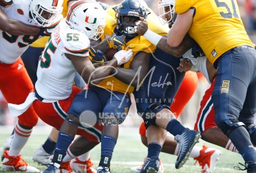 Sep 15, 2018; Toledo, OH, USA; Toledo Rockets running back Shakif Seymour (21) gets tackled by Miami Hurricanes linebacker Shaquille Quarterman (55) and defensive lineman Gerald Willis III (right) during the third quarter at Glass Bowl. Mandatory Credit: Raj Mehta-USA TODAY Sports