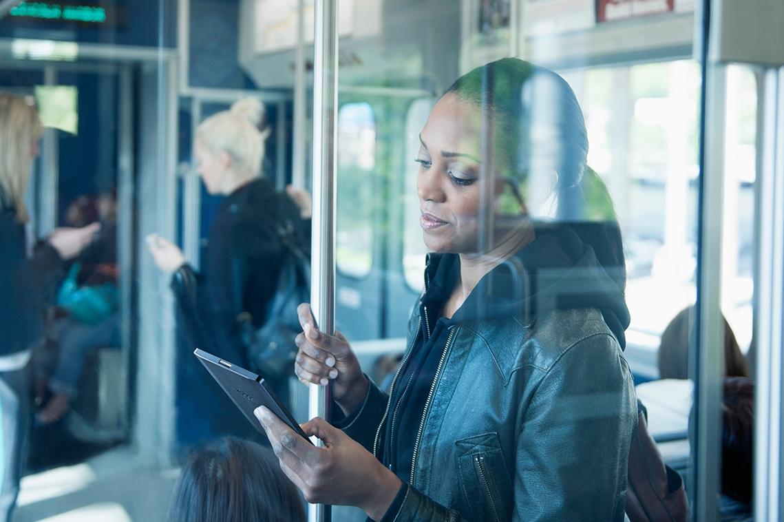 Woman using Kobo eReader on train