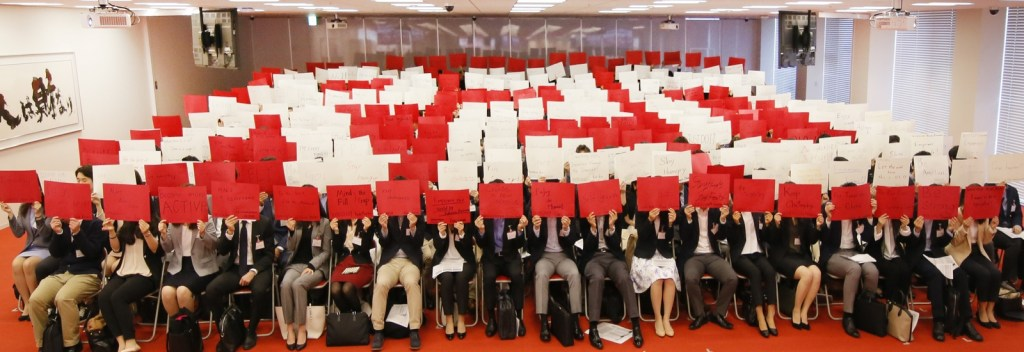 """The new graduates wrote their goals on colored paper, and coordinated at the ceremony to spell the letters """"R20,"""" celebrating Rakuten's 20 years of business."""