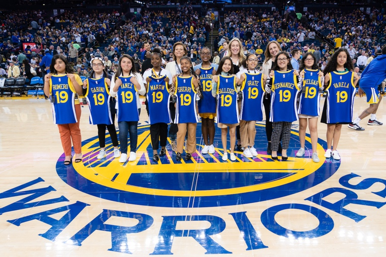 Girls Inc. of Alameda County with Sonya Curry (back left), Adrienne Down Coulson (back center) and Rakuten director of sports and entertainment Kristen Gambetta (back right) being recognized on court during halftime of the Warriors game on March 31.